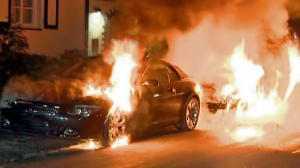 Hořící auta na berlínských ulicích