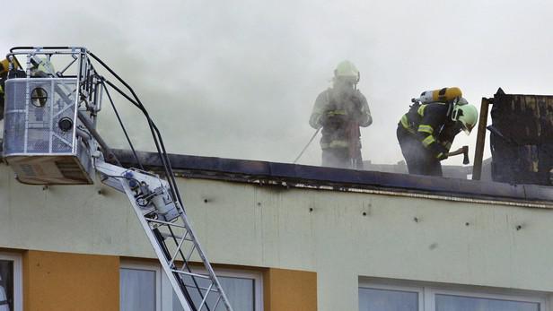 Hasiči hasí hořící střechu