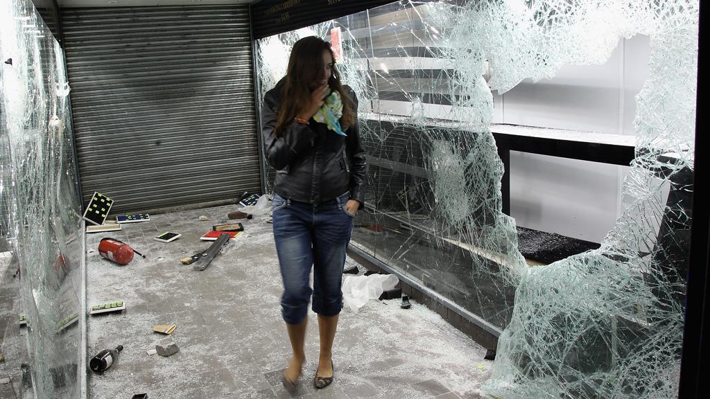 Dívka si prohlíží zničený londýnský obchod