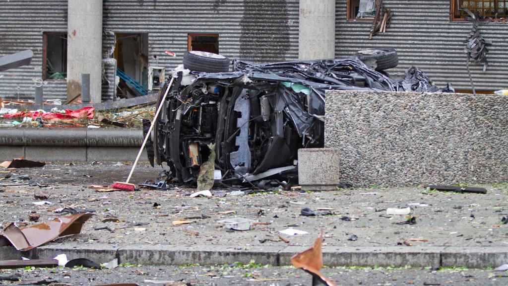 Zdemolovaný vůz před vládní budovou v Oslu