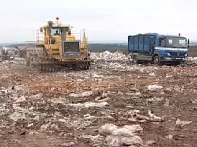 Buldozer upravuje skládku odpadu