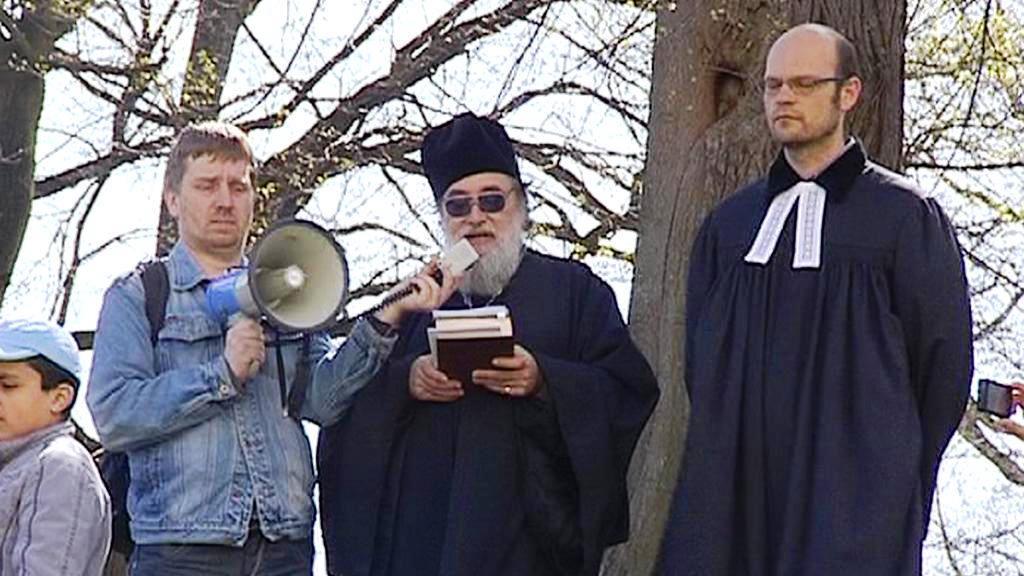 Farář Ludvík Šťastný (uprostřed) při bohoslužbě