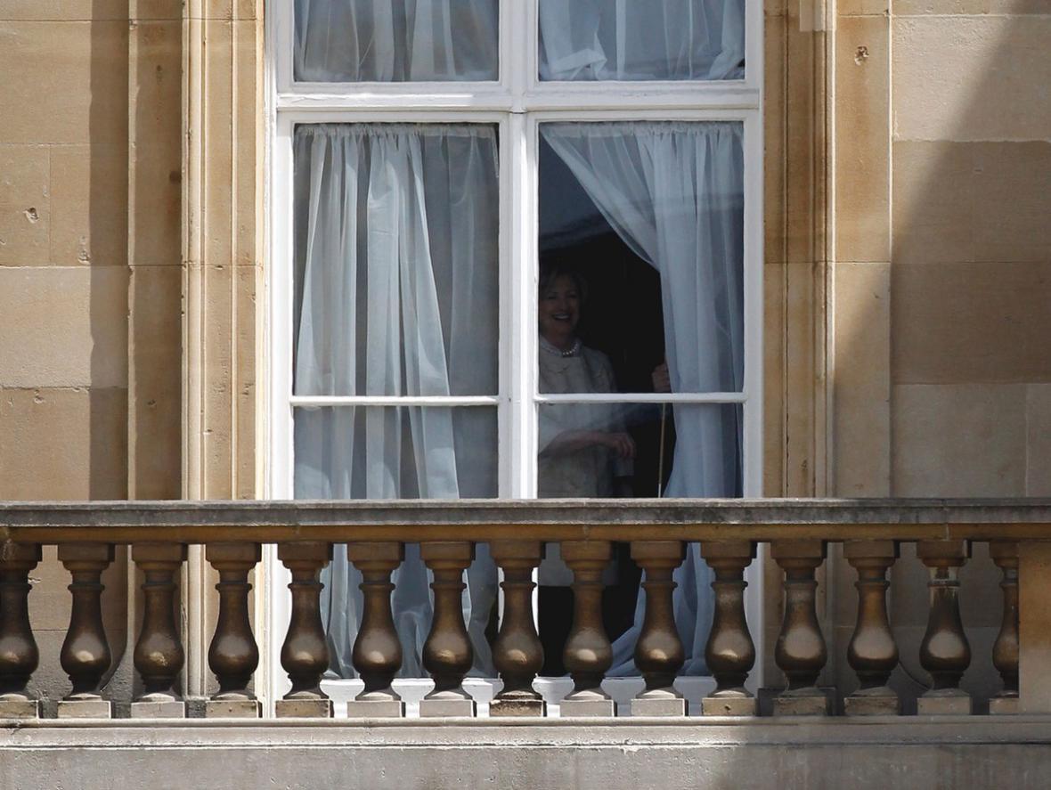 Hillary Clintonová vyhlíží z okna Buckinghamského paláce