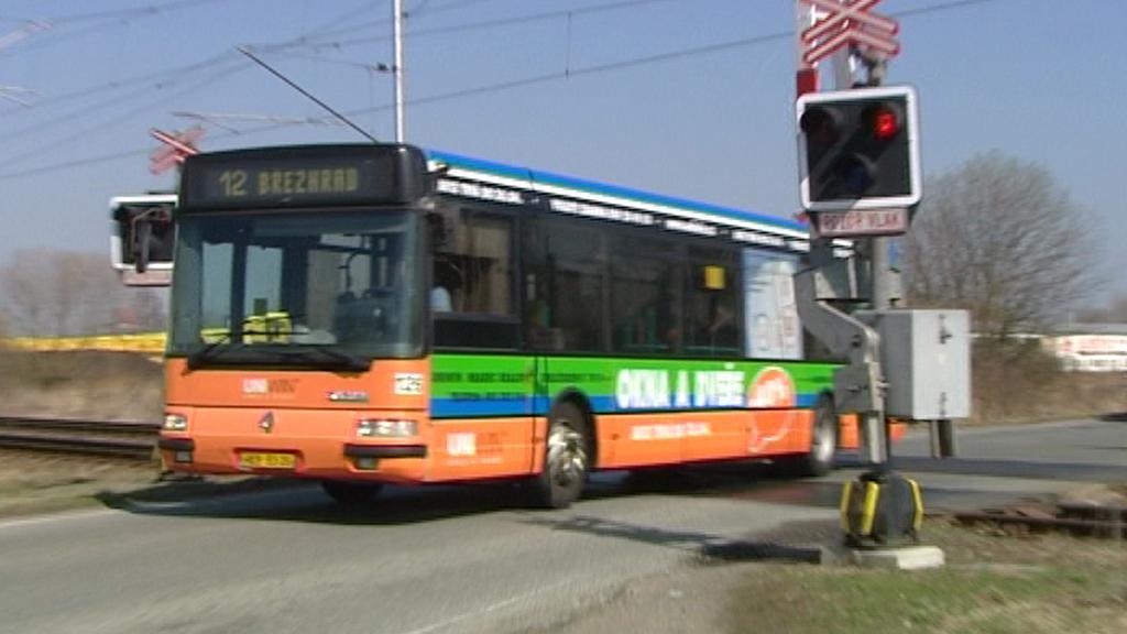 Autobus projíždí přes přejezd na červenou