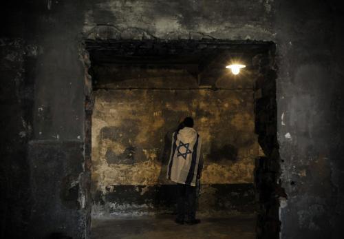 Mladík se modlí během Pochodu živých v osvětimské plynové komoře