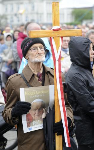 Muž s křížem, který zdobí polská vlajka, sleduje beatifikaci ve Varšavě