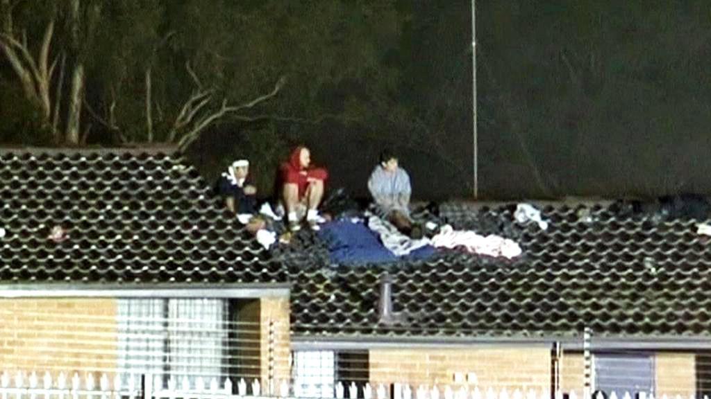 Protestující uprchlíci na střeše azylového centra v Sydney