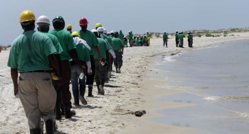 Zástup čističů najatých společností BP na pobřeží ostrova Dauphin