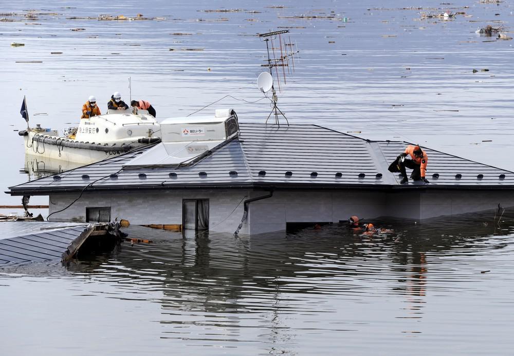 Záchranáři prohledávají dům, který odnesla vlna tsunami na moře