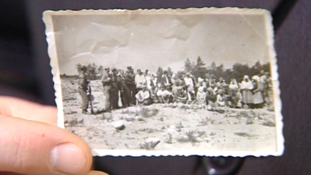 Fotografie Poláků nad hromadným hrobem