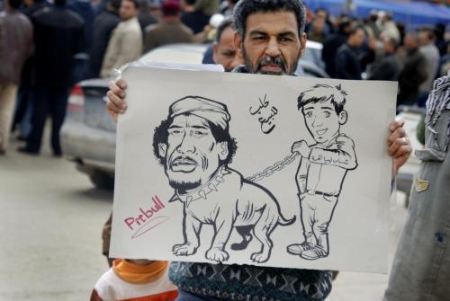 Protestující Libyjec s karitkaturou Muammara Kaddáfího