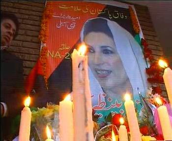 Pákistánci zapalují svíčky u obrazu Bénazír Bhuttové