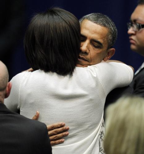 Barack Obama objímá svou ženu na ceremoniálu k uctění památky obětí střelby v Tucsonu