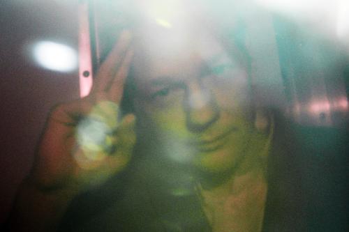 Julian Assange zdraví z policejního vozu