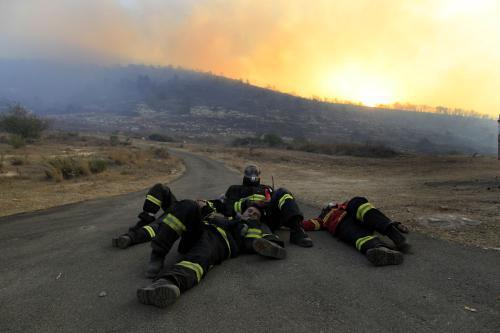 Izraelští hasiči odpočívají po nočním hašení požáru u Haify