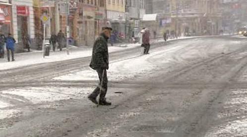 Chodec prochází zledovatělou ulicí