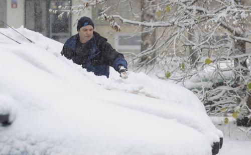 Řidič odklízí sníh z auta