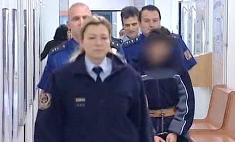 Policisté přivádějí obžalovaného do soudní síně