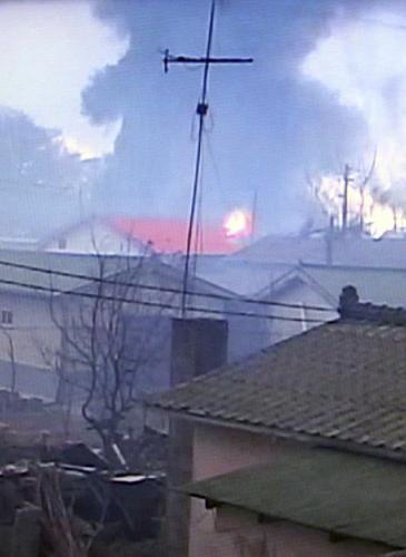 Hořící budovy na ostrově Jon-pchjong