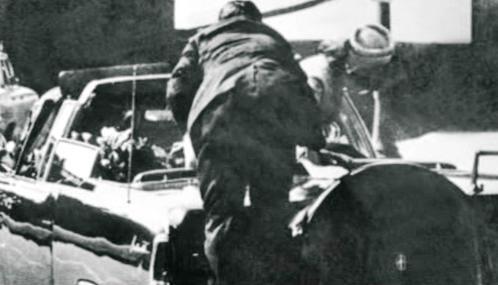 Agent Clint Hill skáče na Kennedyho limuzínu