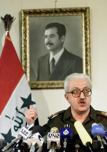 tárik Azíz před portrétem Saddáma Husajna