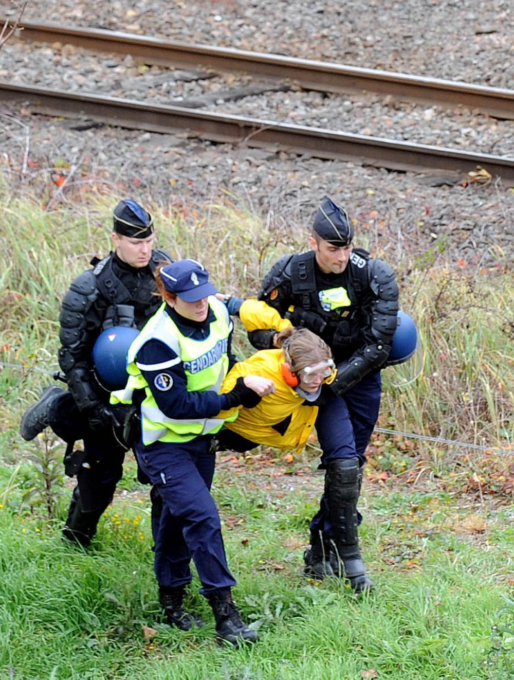 Policisté odnášející demostrantku