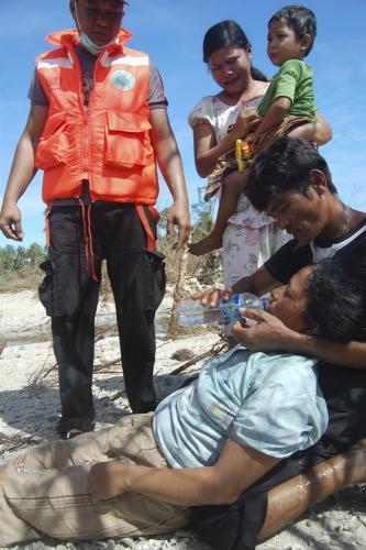 Záchranáři pomáhají ženě, která přežila tsunami na ostrově Pagai