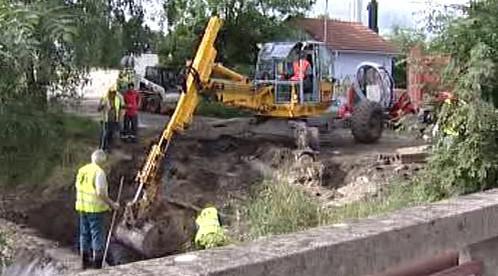 Bagr odstraňuje zeminu z břehu