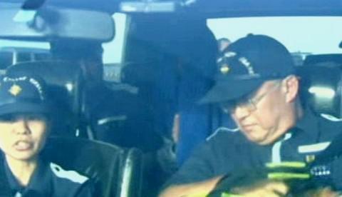 Propuštěný čínský kapitán (vzadu na sedadle)