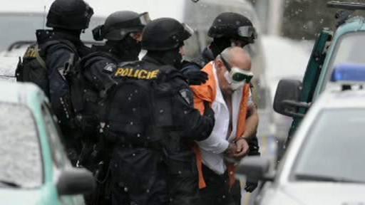 Policisté odvádějí muže z banky