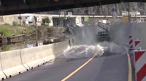 Auto projíždí částečně zaplavenou silnici