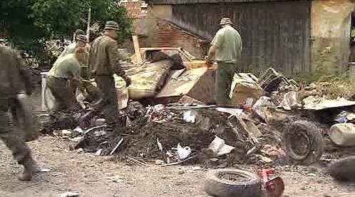 Lidé likvidují odpad po záplavách