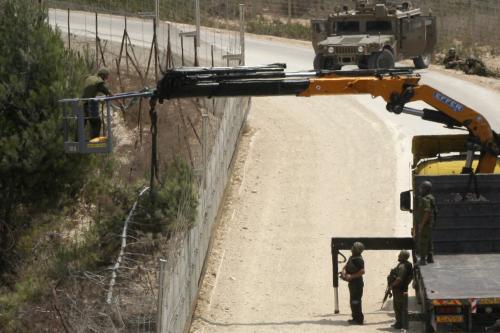 Izraelský ženista opravuje hraniční plot s Libanonem