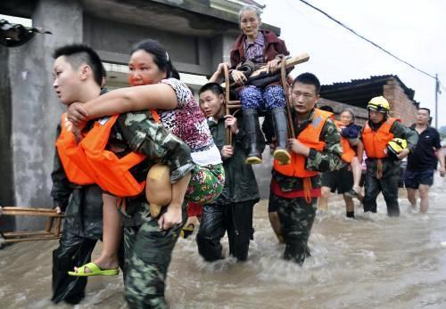 Čínští záchranáři odnášejí lidi zasažené povodněmi