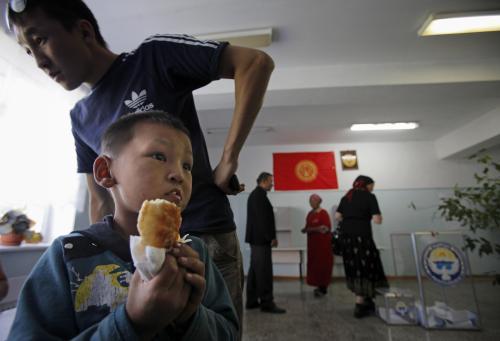 Kyrgyzský chlapec čeká, až rodiče vyjádří svůj hlas