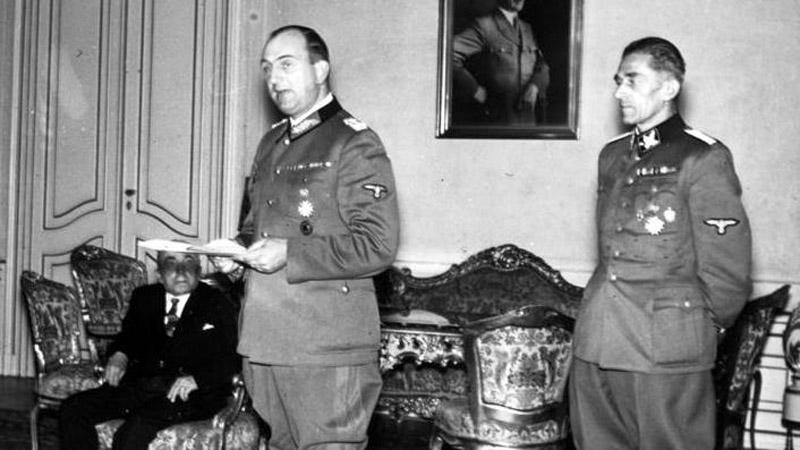 Kurt Daluege a Karl Hermann Frank, v pozadí sedí Emil Hácha