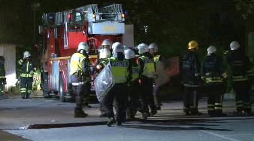 Švédská policie se pokouší bránit hasiče