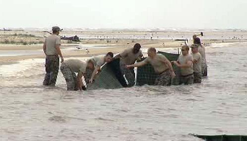 Vojáci vztyčují zábrany proti ropné skvrně