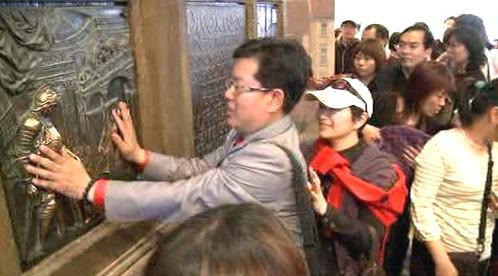 Návštěvníci českého pavilonu si hladí desky ze sochy Jana Nepomuckého