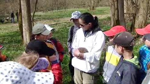 Paní učitelka společně se žáky vypouští ježka do přírody