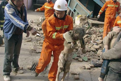 Záchranář vynáší dítě z trosek domu zničeného zemětřesením