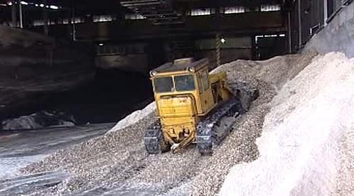 Buldozer rozhrnuje dřevní hmotu