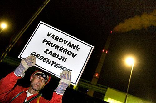 Akvitista Greenpeace před prunéřovskými komíny