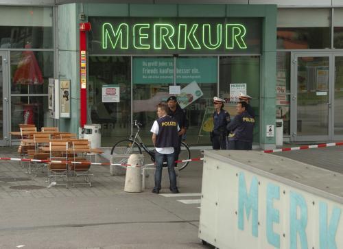Rakouská policie před supermarketem Merkur