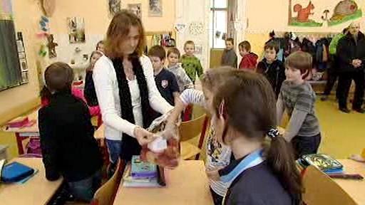 Učitelka rozdává jablka žákům základní školy