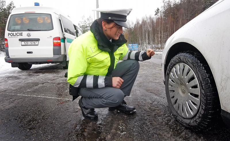 Policistka kontroluje zimní pneumatiku