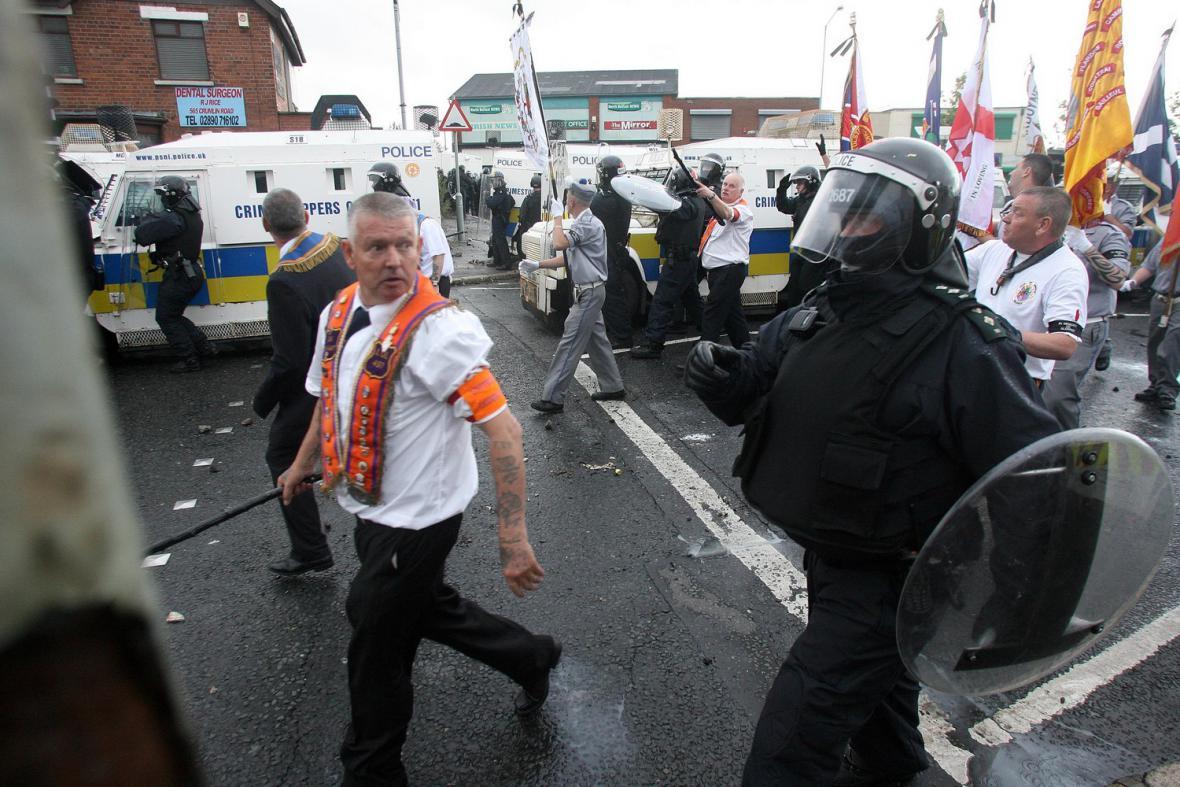 Policisté doprovázející demostrující irské oranžisty