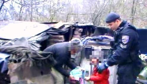 Policista odebírá holčičku její matce