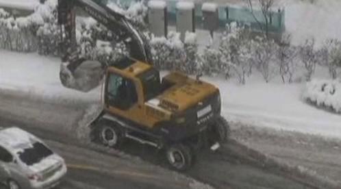 Bagr odklízí sníh v ulicích Pekingu