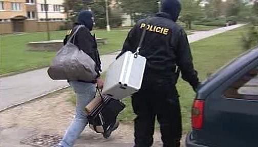 Policisté odnášejí zabavené věci
